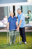 Senior Woman Being Assisted By Male Caretaker Royalty Free Stock Photography