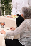Senior woman being served Stock Photo