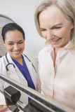 Senior Woman Being Weighed by Doctor Nutritionist. A senior women being weighed on scales by female latina hispanic doctor nutritionist Royalty Free Stock Photos