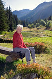 Senior Woman on Bench near Lake in the mountains. Stock Images