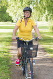Senior woman bicycling in a park at sunny afternoon Royalty Free Stock Photo