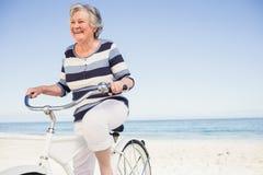 Senior woman on a bike. On the beach Stock Image