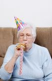 Senior Woman With Birthday Hat Blowing Noise Maker Royalty Free Stock Image