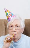 Senior Woman With Birthday Hat And Noise Maker Stock Images