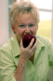 Senior woman biting apple Royalty Free Stock Photos