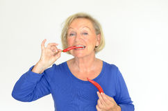 Senior woman biting a red hot chili pepper Stock Images