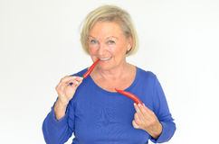 Senior woman biting a red hot chili pepper Stock Photography