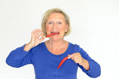Senior woman biting a red hot chili pepper Stock Photos