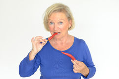 Senior woman biting a red hot chili pepper Royalty Free Stock Photography