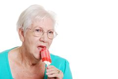 Senior woman biting a red popsicle Royalty Free Stock Photography