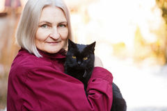Senior woman and the black cat. Photo of beautiful senior woman with black cat Royalty Free Stock Images