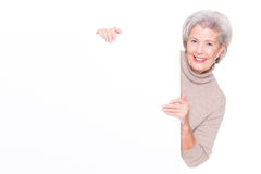 Senior woman with blank sign. In front of white background Stock Photos