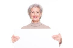 Senior woman with blank sign. In front of white background Royalty Free Stock Image