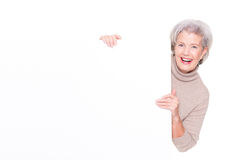 Senior woman with blank sign. In front of white background Stock Photography