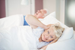 Senior woman blocking ears while man snoring on bed. Irritated senior women blocking ears while men snoring on bed Royalty Free Stock Image