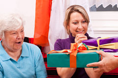 Senior woman and blonde female gets presents Royalty Free Stock Image