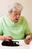 Senior woman in blood sugar measure is surprised Royalty Free Stock Images