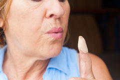 Senior Woman blowing band aid finger wound Stock Images