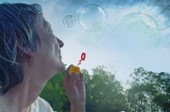 Senior woman blowing bubbles royalty free stock image