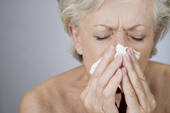 A senior woman blowing her nose Royalty Free Stock Photos