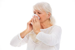 Senior woman blowing her nose Royalty Free Stock Photo