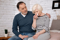 Senior woman blowing her nose near husband. Do not mind. Senior nice women is crying near her aged husband trying give her solace Stock Photo
