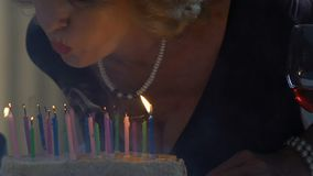 Senior woman blowing out candles on cake, surprise for birthday anniversary. Stock footage stock footage