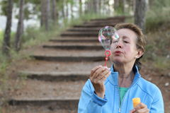 Senior woman blowing soap bubbles in summer park with copy space Stock Image