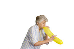 senior woman blowing up yellow balloon, cut out Royalty Free Stock Photos