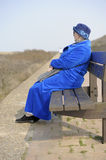 Senior woman in blue seated on a bench Royalty Free Stock Images