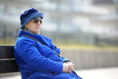 Senior woman in blue sitting on a bench Royalty Free Stock Photo