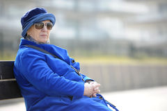 Senior woman in blue sitting on a bench Stock Photo