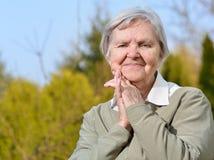 Senior woman on blue sky. Stock Photos