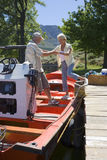 Senior woman boarding motorboat moored at lake jetty, husband offering helping hand, smiling, side view Stock Images