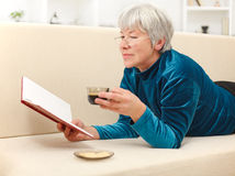 Senior woman with book and coffee Stock Photography