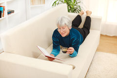 Senior woman with book and coffee Stock Photos