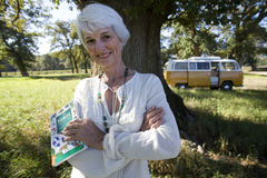 Senior woman with book in field, camper van in background, smiling, portrait Royalty Free Stock Images