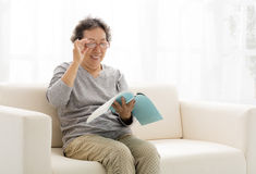 Senior woman with book in living room Royalty Free Stock Image