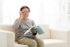 senior woman with book in living room Stock Images