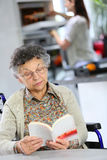 Senior woman with a book sitting at the table Royalty Free Stock Images