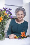 Senior Woman Beside Bouquet of Flowers in the Kitchen, Portrait Stock Images