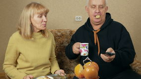 Senior woman brings a man to a tray of tea and biscuits. They choose a TV program and relaxing together at home on the stock footage
