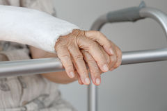 Senior woman with broken arm using walker. Royalty Free Stock Photos