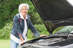 Senior woman with broken car Stock Photo