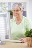 Senior woman browsing internet at home Royalty Free Stock Images