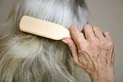 Senior woman brushing her hair Royalty Free Stock Image