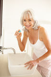 Senior Woman Brushing Teeth In Bathroom Stock Images