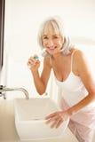 Senior Woman Brushing Teeth In Bathroom. Mirror stock images