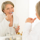 Senior woman brushing teeth bathroom mirror. Senior woman brushing teeth looking at herself in bathroom mirror royalty free stock photos