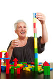 Senior woman building block tower Royalty Free Stock Image